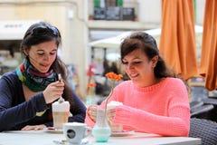 Deux jeunes femmes buvant du cappuccino Image stock