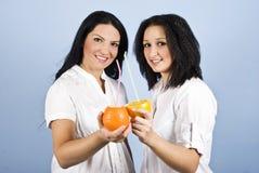 Deux jeunes femmes buvant du jus d'agrumes Image libre de droits