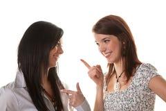 Deux jeunes femmes chuchotent ensemble Photo stock