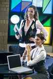 Deux jeunes femmes contactant des ordinateurs portatifs à la table Photo libre de droits