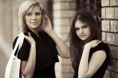 Deux jeunes femmes contre le mur de briques Image libre de droits