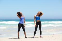 Deux jeunes femmes convenables appréciant la séance d'entraînement à la plage Photographie stock