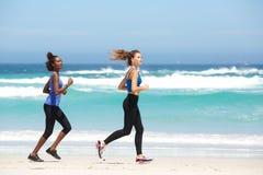 Deux jeunes femmes convenables courant le long de la plage Images libres de droits