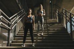 Deux jeunes femmes courant dans le milieu urbain photographie stock