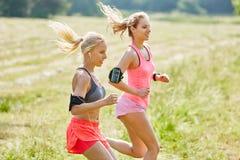 Deux jeunes femmes courant ensemble Images stock