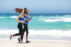 Deux jeunes femmes courant le long de la plage Photographie stock libre de droits