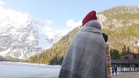 Deux jeunes femmes couvertes dans les couvertures regardant les montagnes et appréciant la vue banque de vidéos