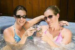 Deux jeunes femmes détendant dans un jacuzzi Photographie stock libre de droits