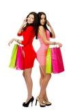 Deux jeunes femmes d'achats parlant par le téléphone Photos stock