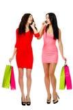 Deux jeunes femmes d'achats parlant par le téléphone Photo stock