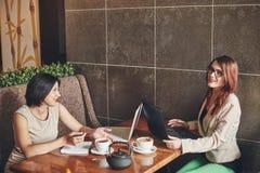 Deux jeunes femmes d'affaires caucasiennes avec l'ordinateur portable, carnet Femmes en café Images stock
