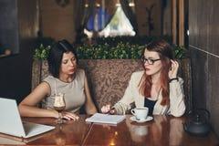 Deux jeunes femmes d'affaires caucasiennes avec l'ordinateur portable Femmes en café Images libres de droits