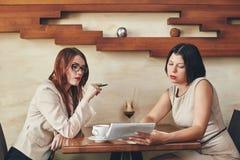 Deux jeunes femmes d'affaires caucasiennes avec le carnet Femmes en café Photographie stock