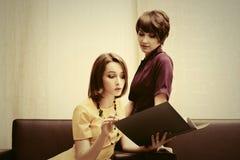 Deux jeunes femmes d'affaires de mode avec un dossier au bureau Image stock