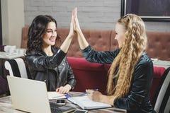Deux jeunes femmes d'affaires donnant haut cinq au café tout en se reposant à la table devant l'ordinateur portable La célébratio photos libres de droits