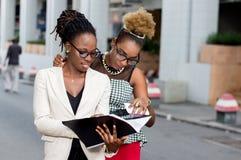Deux jeunes femmes d'affaires lisant un document photographie stock libre de droits