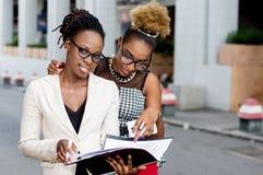 Deux jeunes femmes d'affaires lisant un document images stock
