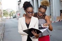 Deux jeunes femmes d'affaires lisant un document photo stock