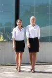Deux jeunes femmes d'affaires marchant dans la rue Photo stock