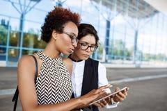 Deux jeunes femmes d'affaires réussies regardant le comprimé sur le centre d'affaires Image libre de droits