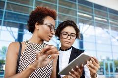 Deux jeunes femmes d'affaires réussies regardant le comprimé sur le centre d'affaires Photographie stock libre de droits