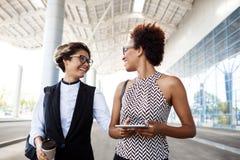 Deux jeunes femmes d'affaires réussies riant, souriant sur le centre d'affaires Photographie stock libre de droits