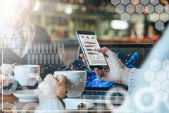Deux jeunes femmes d'affaires s'asseyant à la table, au café potable et analysant des données Sur l'ordinateur portable de table  image stock