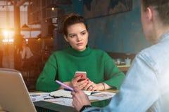 Deux jeunes femmes d'affaires s'asseyant à la table le restaurant et en parlant Sur la table est l'ordinateur portable, carnet, d Photo stock