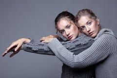 Deux jeunes femmes dans des chandails gris sur le fond gris beau g Photos libres de droits