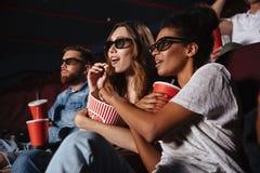 Deux jeunes femmes dans des lunettes observant le film 3d Images stock