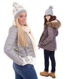 Deux jeunes femmes dans des vêtements d'hiver d'isolement sur le blanc Images stock