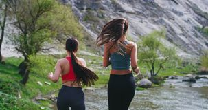 Deux jeunes femmes dans des vêtements de sport à la nature sont prêtes pour commencer leur moment d'exercices de séance d'entraîn clips vidéos