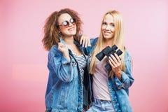 Deux jeunes femmes dans des vestes de jeans de denim avec des lunettes de soleil et des jumelles Photos stock
