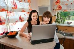 Deux jeunes femmes dans la cuisine avec un ordinateur portatif Image stock