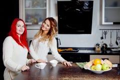 Deux jeunes femmes dans la cuisine parlant et mangeant du fruit, mode de vie sain, filles vont faire des smoothies Image libre de droits