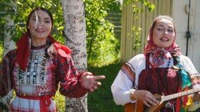 Deux jeunes femmes dans le support traditionnel russe de robe sous un arbre et une danse de bouleau clips vidéos