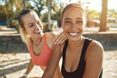 Deux jeunes femmes dans les vêtements de sport riant après une séance d'entraînement extérieure images libres de droits