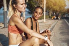 Deux jeunes femmes dans les vêtements de sport riant après une séance d'entraînement extérieure photographie stock libre de droits