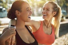 Deux jeunes femmes dans les vêtements de sport riant après une séance d'entraînement extérieure images stock