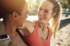 Deux jeunes femmes dans les vêtements de sport riant après une séance d'entraînement extérieure photos libres de droits