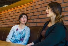Deux jeunes femmes de brune s'asseyant dans un café ayant la conversation Image stock