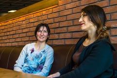 Deux jeunes femmes de brune s'asseyant dans un café ayant la conversation Images libres de droits