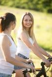 Deux jeunes femmes de cycliste en parc Photographie stock libre de droits