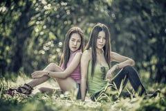 Deux jeunes femmes de l'Asie s'asseyant sur l'herbe Image libre de droits