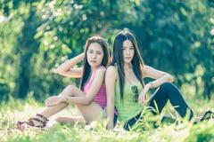 Deux jeunes femmes de l'Asie s'asseyant sur l'herbe Photos stock