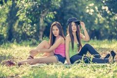 Deux jeunes femmes de l'Asie s'asseyant sur l'herbe Photo libre de droits