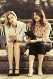 Deux jeunes femmes de mode à l'aide des tablettes extérieures Photographie stock