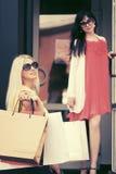 Deux jeunes femmes de mode avec des paniers dans le mail Images stock