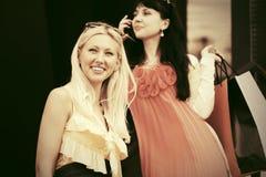 Deux jeunes femmes de mode avec des paniers sur la rue de ville Images libres de droits