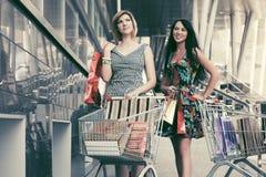 Deux jeunes femmes de mode avec le caddie dans le mail Photo stock